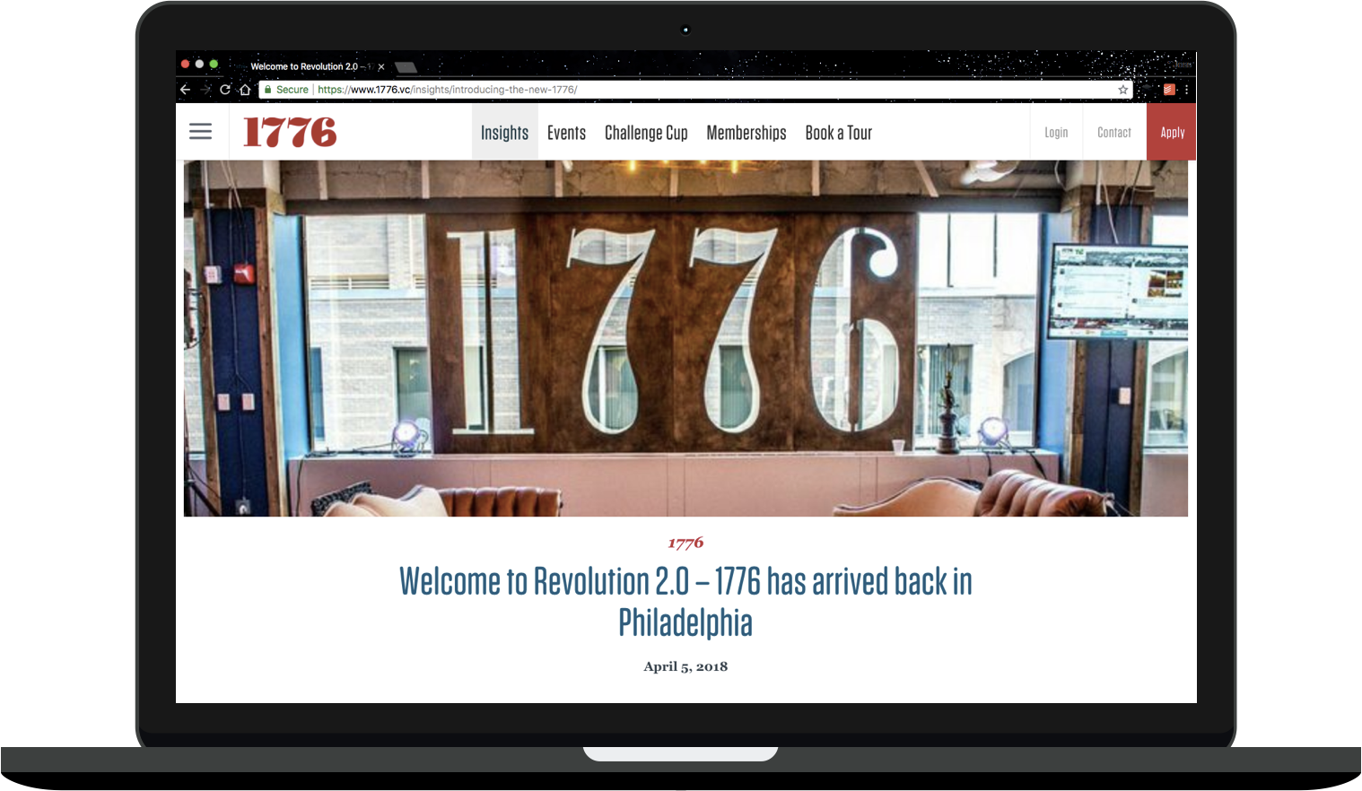 "A mockup of a MacBook depicts the 1776 website. There's a photo of what looks like a living room - couches, a coffee table - with giant wood letters behind it that spell ""1776."" Beneath the photo is a headline that reads ""Welcome to Revolution 2.0 - 1776 has arrived back in Philadelphia."""