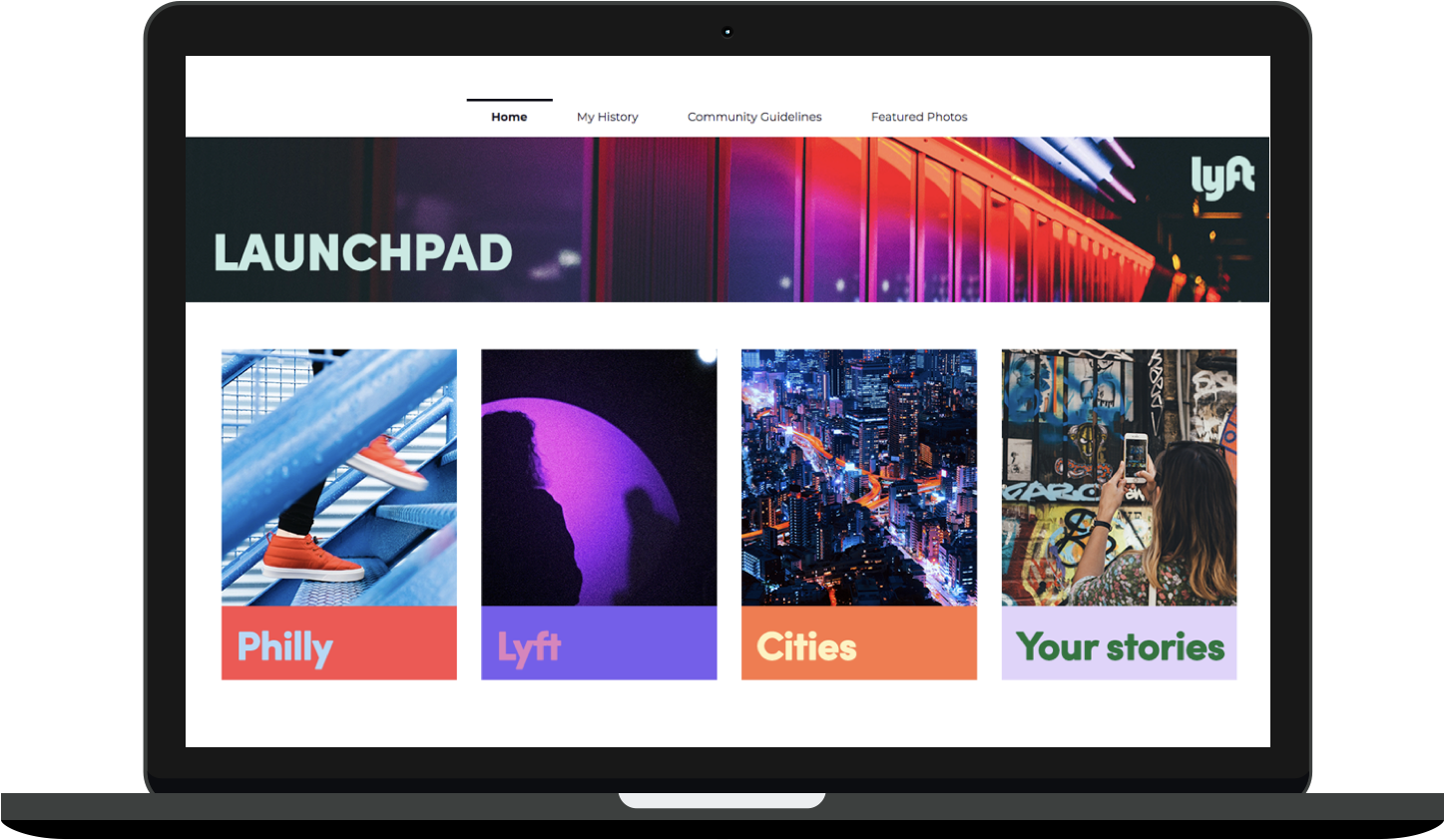 A Macbook screen depicting the Launchpad platform. There are four main sections: Philly (with a photo of feet climbing stairs), Lyft (with a photo of people silhouetted against a glowing orb), Cities (with a photo of a neon-colored skyline), and Your Stories (with a photo of a woman taking a picture of graffiti with her phone).